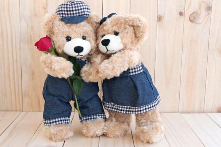 twee teddyberen met roos op houten achtergrond, love concept voor Valentijnsdag, huwelijk en verjaardag Stockfoto