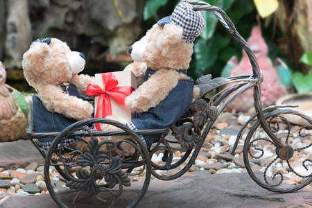 teddy bear love: two teddy bears with a bicycle on garden background, love concept for valentines day, wedding and anniversary