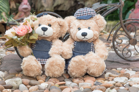 teddy bear love: two teddy bears with roses on garden background, love concept for valentines day, wedding and anniversary