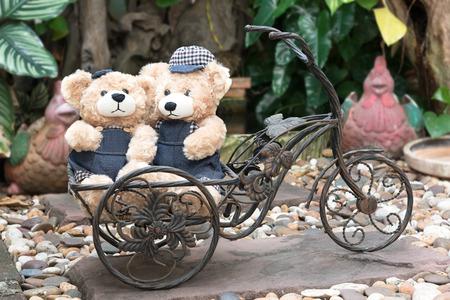 enamorados caricatura: Dos osos de peluche con una bicicleta en el fondo del jard�n, el concepto de amor Foto de archivo