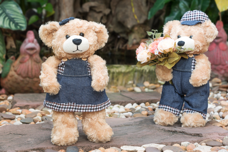 love image: two teddy bears with roses on garden background, concept love Stock Photo