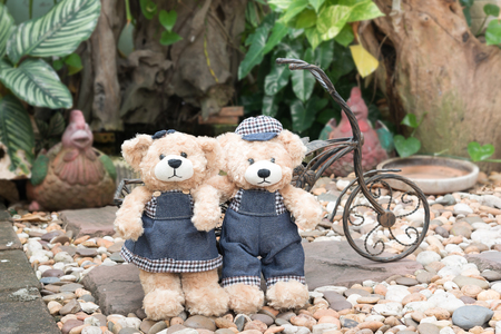 soul mate: two teddy bears with a bicycle on garden background, concept love