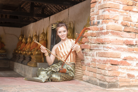 attire: Thai lady in vintage original thailand attire and fiddle Editorial