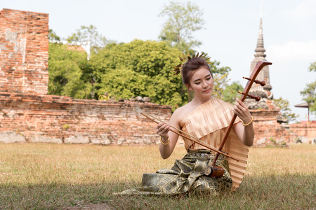 fiddles: Thai lady in vintage original thailand attire and fiddle Stock Photo