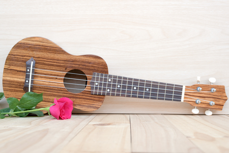 acoustic ukulele: pink rose and ukulele on wooden background with space, love concept