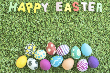 and spelling: colorful easter eggs on green grass background and text happy easter word spelling, with copy space Stock Photo