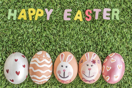 and spelling: text happy easter word spelling and colorful easter eggs on green grass background, with copy space