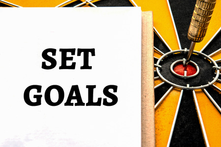 investment goals: Words set goals with dart target arrow on the center of dartboard, Smart goal target success business investment financial strategy concept, abstract background
