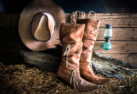 barn boots: Still life with american west rodeo brown felt cowboy hat and traditional leather boots in vintage ranch barn background Stock Photo