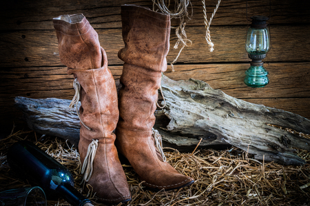 barn boots: Still life photography with traditional leather boots in vintage ranch barn background Stock Photo