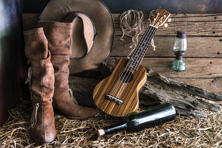 brown leather hat: Still life photography with ukulele on american west rodeo brown felt cowboy hat and traditional leather boots in vintage ranch barn background Stock Photo