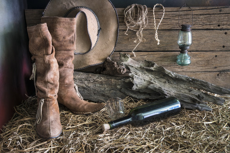 brown leather hat: Still life painting photography with traditional leather boots and american west rodeo brown felt cowboy hat in vintage ranch barn background Stock Photo