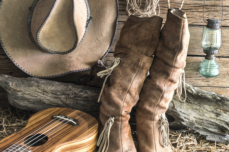 brown leather hat: Closeup american west rodeo brown felt cowboy hat and traditional leather boots with ukulele in vintage ranch barn background, Still life style Stock Photo