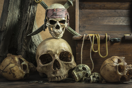 coffer: closeup pirate skull with two swords over on human skull pile awesome and treasure coffer background still life style, pirate concept for halloween