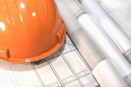 architect tools: blueprints rolls and orange helmet over architectural plans project drawing, architect engineering and contractor concept