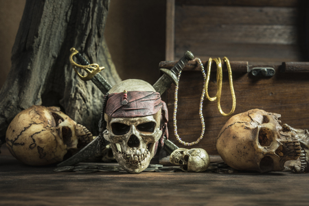 coffer: pirate skull with two swords and treasure coffer over three head of human background still life style, pirate concept for halloween