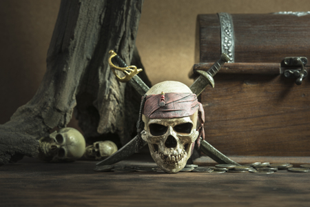 pirate skull with two swords and coffer over two head of human background still life style, pirate concept for halloween