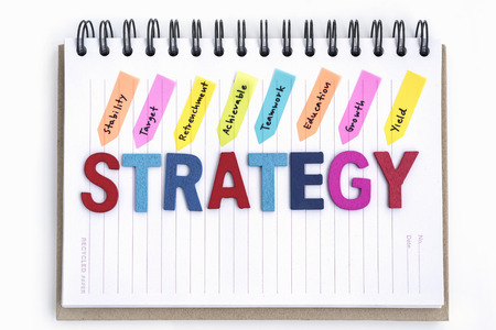 achievable: words strategy on the notebook with handwriting stability target retrenchment achievable teamwork education growth yield over white background, Business strategy concept