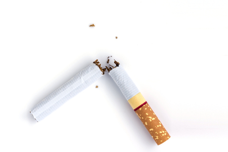 Quit smoking, closeup broken cigarette on white background, soft focus