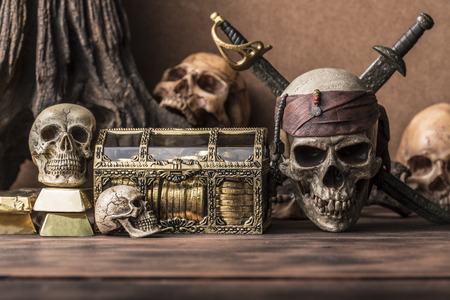 pirate skull and human skeleton with gold and treasure coffer halloween concept still life style