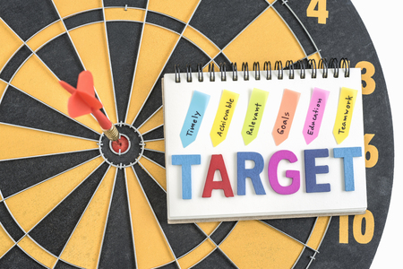 achievable: dart target in bullseye with words target on the notebook with handwriting timely achievable relevant goals education teamwork over dartboard background, Business success concept