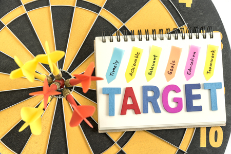 achievable: six dart in bullseye with words target on the notebook with handwriting timely achievable relevant goals education teamwork over dartboard background, Business success concept Stock Photo