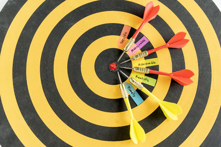 measurable: words smart goals specific measurable achievable realistic timely with five dart target near bullseye over dartboard with copy space, Business success concept Stock Photo