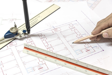 pencil point: hand holding pencil point to architectural plans project drawing, architect engineering and contractor concept Stock Photo