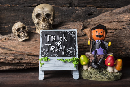 Jack-o-lantern in witch suit sitting on a tree with trick or treat board over two human skull background