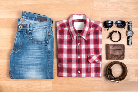 Mens casual outfits with accessories on wooden table, Red plaid shirt and blue jeans with eyeglasses, bracelet, wallet, brown belt and watch, top view