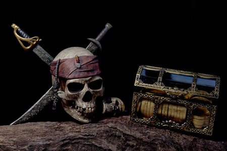 Pirate skull with two swords and coffer with head of human over darkness background, still life style Stock Photo