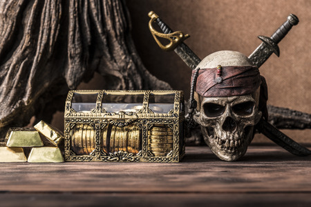 coffer: still life photography with pirate skull holding two swords and treasure coffer, gold bar,  bullion. Halloween concept