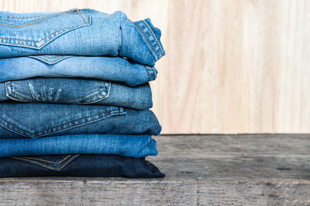 unisex: Jeans stacked on a wooden table, unisex trendy fashion