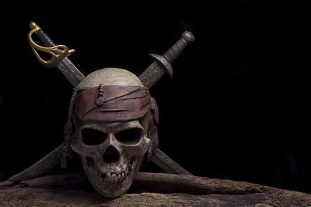 Cranio del pirata con due spade sull'oscurità fondo stile di vita ancora Archivio Fotografico - 68035665