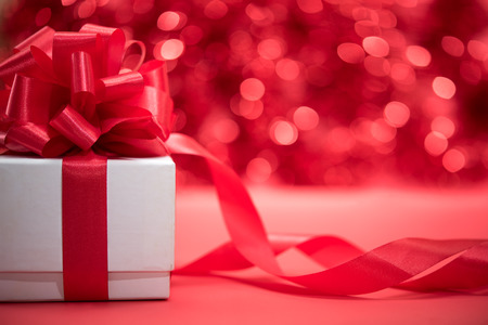 White gift box wrap with red ribbon bow over abstract blur festive light bokeh background with copy space Stock Photo