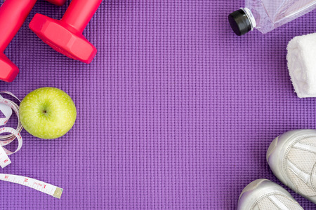 Fitness background with red dumbbells, green apple, sport shoes, white towel, water and measuring tape over violet yoga mat with copy space. Healthy and lifestyle concept