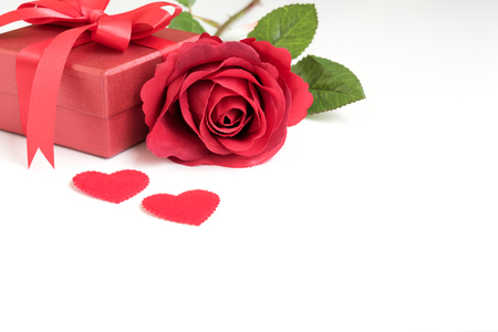 Red rose with gift box and two hearts on white background with copy space