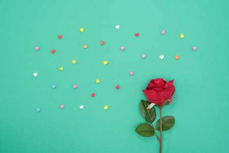 minimal: Red rose with glitter hearts on green paper background minimal style