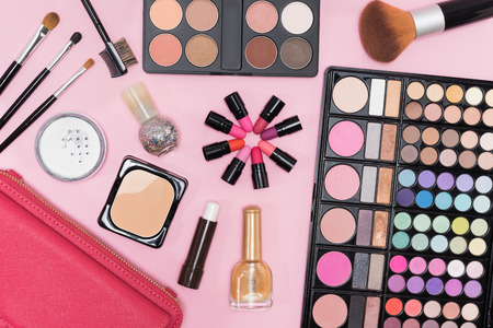 Collection of makeup cosmetics palette, lipstick, nail polish and brushes on pink background flat lay top view
