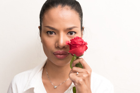 think about: Close up Beautiful asian women closed her eye and think about love with red rose with copy space, Woman day concept
