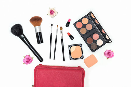 Collection of makeup cosmetics palette, lipstick and brushes on white background with pink roses flat lay top view