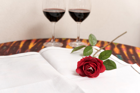 woo: Marriage proposal concept with Diamond ring inside red rose over two wine glasses background with copy space