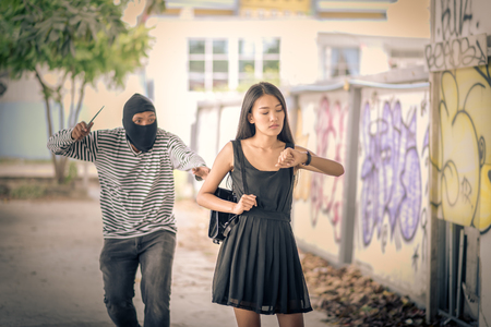 Street thief holding knife and trying to steal and run away the shoulder bag while woman looking watch, Vintage tone style  Stock Photo