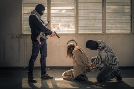 Gijzelaar van terrorist of inbreker dreigen met geweer en bind met touwen in het oude verlaten gebouw Stockfoto