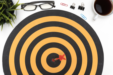 Dart Target Arrow Hitting On Bullseye In Dartboard Over Office Desk Table  Background With Eye Glasses
