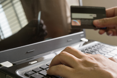 Hand holding a credit card and using laptop for online shoping on the internet at home, IOT internet of things concept Stock Photo