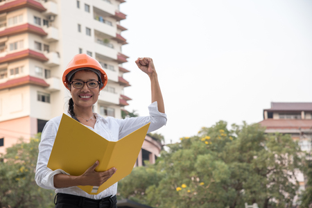 Portrait of beautiful confident young woman working smiling happy, looking at camera over construction site background