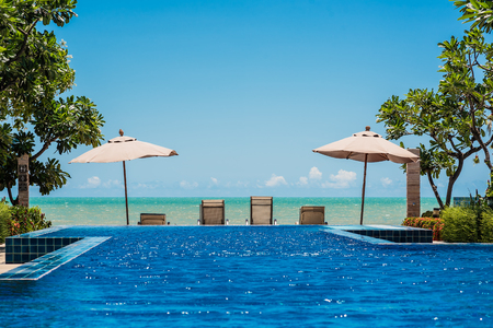 Tropical beach resort with lounge chairs and umbrella with the sea and blue sky background