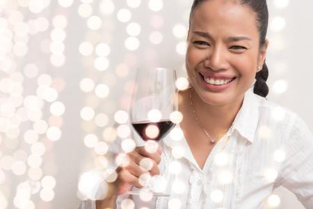 Beautiful woman celebrating with night light and hold wine glass. Standard-Bild
