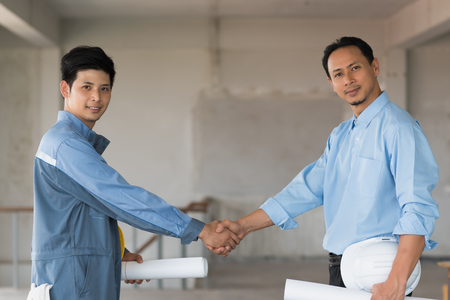 Confidence businessman shaking hands to seal a deal with engineer in building, Business success concept Stock Photo